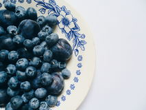 Berries of blueberries and plums on a white plate Royalty Free Stock Photography