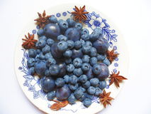 Berries of blueberries and plums on a white plate Stock Images