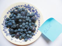 Berries of blueberries and plums on a white plate Royalty Free Stock Photo