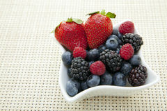 Berries in a bowl. Fresh berries in an ornate bowl on a placemat Stock Image
