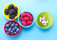 Berries in bowls. Berries and dietary supplements in colorful bowls viewed from above, on blue surface stock photo