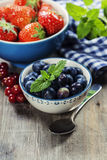 Berries in bowls  on Wooden Background. Royalty Free Stock Images