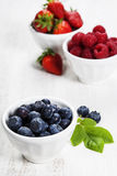 Berries in bowls  on Wooden Background. Stock Images