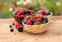 Berries in bowls. On wooden table in a garden, fruits, cherry, raspberry, strawberry and bluberry Stock Photo