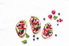 Berries bruschetta on a light background, top view. Sandwiches with cream cheese, raspberries, red and black currants. Delicious b. Reakfast, snack. Flat lay royalty free stock images