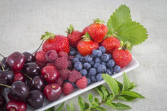 Berries and cherries. Several fruits on mint on a table Royalty Free Stock Photography