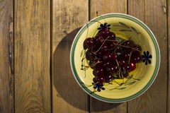 Berries cherry, behind the plate, standing on a wooden backgroun Royalty Free Stock Photos
