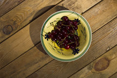 Berries cherry, behind the plate, standing on a wooden backgroun Stock Image