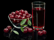Berries of a cherry and juice on a black background. Royalty Free Stock Images
