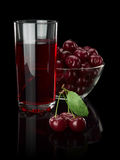 Berries of a cherry and juice on a black background. Stock Image