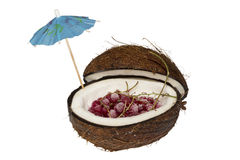 Berries in the coconut. Red currant is in coconut with an umbrella Royalty Free Stock Photo