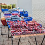 Berries in containers for sale. Cherries, strawberries, blueberries, raspberries, gooseberries in transparent blue boxes in the farmers` market Stock Photography