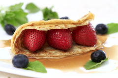 Berries Crepe. Strawberry and blueberry crepe with maple syrup royalty free stock images