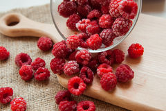 Berries on a cutting board. Prepare dessert. Frozen raspberries in a glass bowl Royalty Free Stock Photography