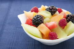 Berries and diced melon in a bowl on the table. Fresh berries and diced melon in an ornate white bowl on a blue placemat Royalty Free Stock Images