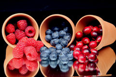 Berries. Different kinds of Berries in earthen container and their reflections royalty free stock photos