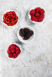 Berries in four bowls from above on marble background. Healthy snacks in bowls , raspberries, blackberries, redcurrants on marble background with copy space Royalty Free Stock Images