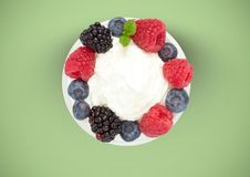 Berries fruit with cream on plate against green background Royalty Free Stock Image