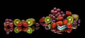 Berries and fruits on a black background Stock Photos