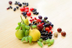 Berries, fruits, vegetables and nuts mixed on the table. Berries, fruits, vegetables and nuts randomly scattered on a table Stock Photos