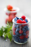 Berries in glass jars on a wooden table and a branch with a flow. Er and raspberry leaves stock photo