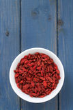 Berries of goji in bowl. On blue background royalty free stock photography