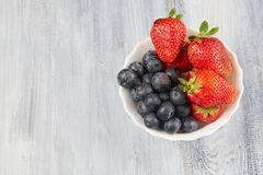 Berries on a gray wooden background. Berries in a white plate on a gray wooden background stock photography