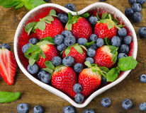 Berries in heart shaped bowl. Healthy eating concept. Royalty Free Stock Photos