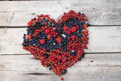 Berries heart on wooden background. Berries heart on wooden old planks background Stock Photo