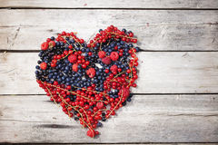 Berries heart on wooden background. Berries heart on wooden plank old background, black and red currant Royalty Free Stock Images