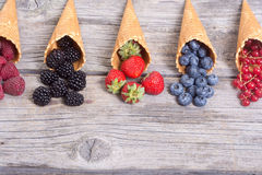 Berries in ice cream cone. Raspberry , blueberry , strawberry , red currant , blackberry with space for text royalty free stock image