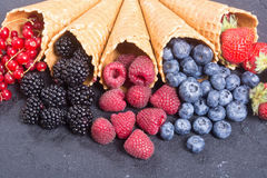 Berries in ice cream cone. Raspberry , blueberry , strawberry , red currant , blackberry Top view with space for text stock photos