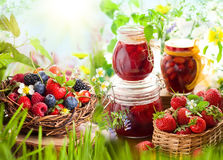Berries  and  jam. Fresh summer berries in baskets and homemade jam in jars Stock Photo