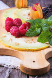 Berries, mint and melon on wooden cutting board. Mix of raspberries, blackberries, mint, physalis and melon on wooden cutting board over wooden table Royalty Free Stock Photography