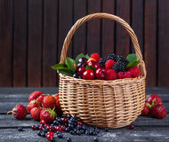 Berries mix in basket on rustic wooden background Royalty Free Stock Images