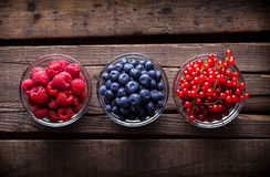 Berries mix in a studio in glass jars. Berries mix in a studio in three glass jars on old rustic wooden table Stock Photography