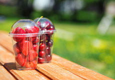 Berries in plastic cup. Strawberry and cherry berries in plastic cup in a summer park Stock Photos