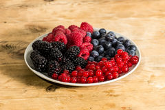 Berries in a plate on a wooden table Stock Photos