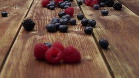 Berries, raspberries, blackberry, blueberries, bramble, dewberry, plate, blue background, small fruity, grain, seed, kernel, granu stock video footage