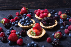 Berries : raspberries , blueberries , blackberries , strawberrie. S. Fresh summer berries in a tartlets on a stone background Stock Images