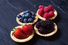 Berries : raspberries , blueberries , blackberries , strawberrie. S. Fresh summer berries in a tartlets on a stone background Stock Photo