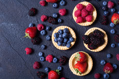 Berries : raspberries , blueberries , blackberries , strawberrie. S. Fresh summer berries in a tartlets on a stone background Royalty Free Stock Photography