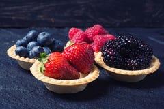 Berries : raspberries , blueberries , blackberries , strawberrie. S . Fresh summer berries in a tartlets on a stone background Stock Photo