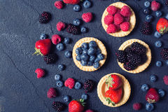 Berries : raspberries , blueberries , blackberries , strawberries. Fresh summer berries in a tartlets on a stone background royalty free stock images