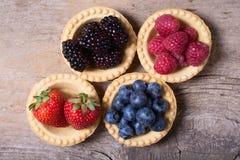 Berries : raspberries , blueberries , blackberries , strawberrie. S. Fresh summer berries in a tartlets on a wooden background Royalty Free Stock Photo
