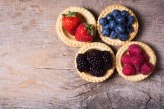 Berries : raspberries , blueberries , blackberries , strawberrie. S . Fresh summer berries in a tartlets on a wooden background Royalty Free Stock Photos