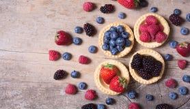 Berries : raspberries , blueberries , blackberries , strawberrie. S . Fresh summer berries in a tartlets on a wooden background Stock Image