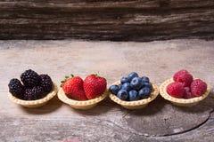 Berries : raspberries , blueberries , blackberries , strawberrie. S . Fresh summer berries in a tartlets on a wooden background Royalty Free Stock Photography