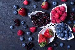 Berries : raspberries , blueberries , blackberries , strawberrie. S. Fresh summer berries in a white bowl on a stone background Stock Photography