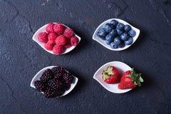 Berries : raspberries , blueberries , blackberries , strawberrie. S. Fresh summer berries in a white bowl on a stone background Stock Photo